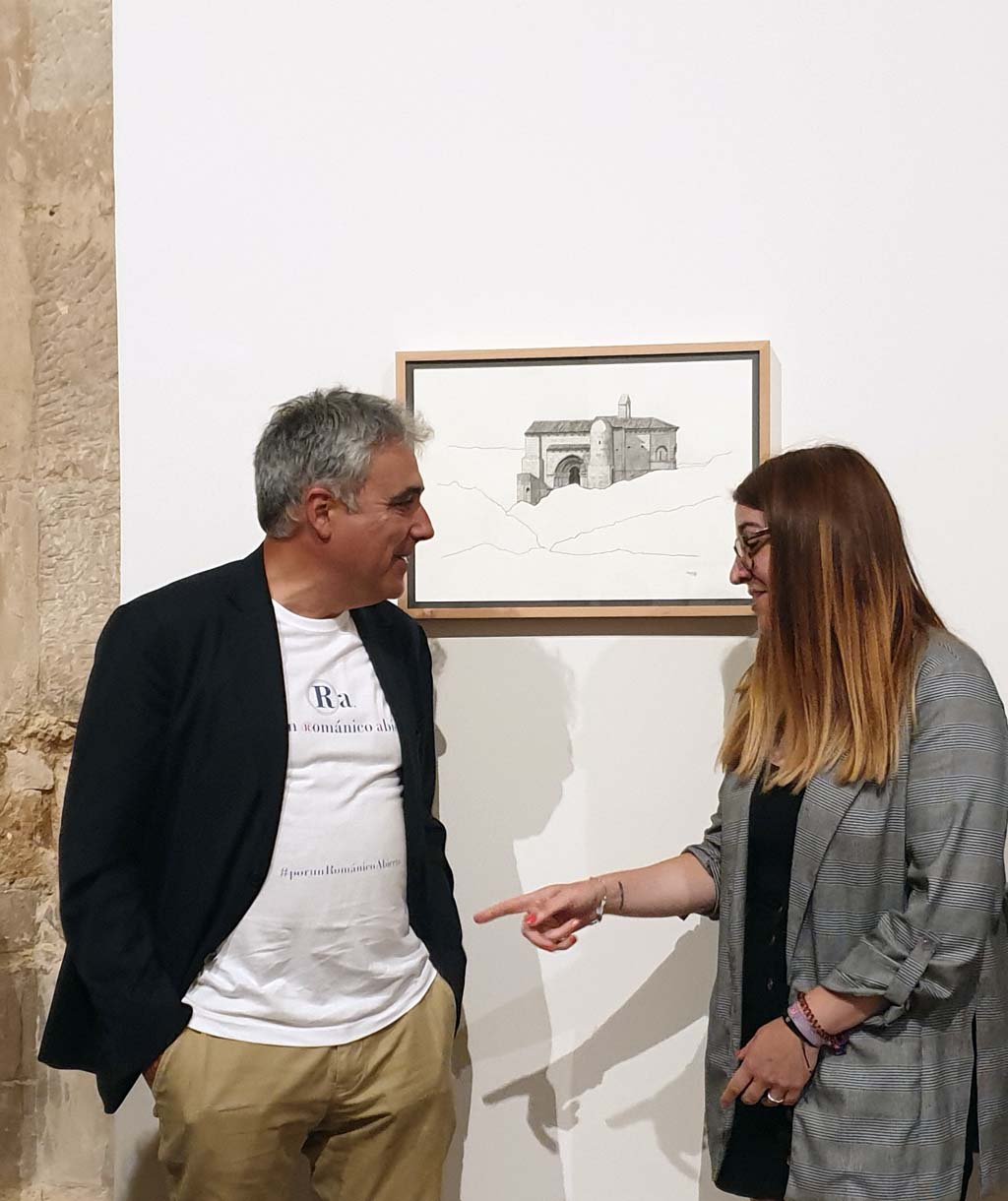 Juan Carlos Prieto charlando con la historiadora Cristina Párbole junto al dibujo de ermita de Santa Cecilia en Vallespinoso de Aguilar